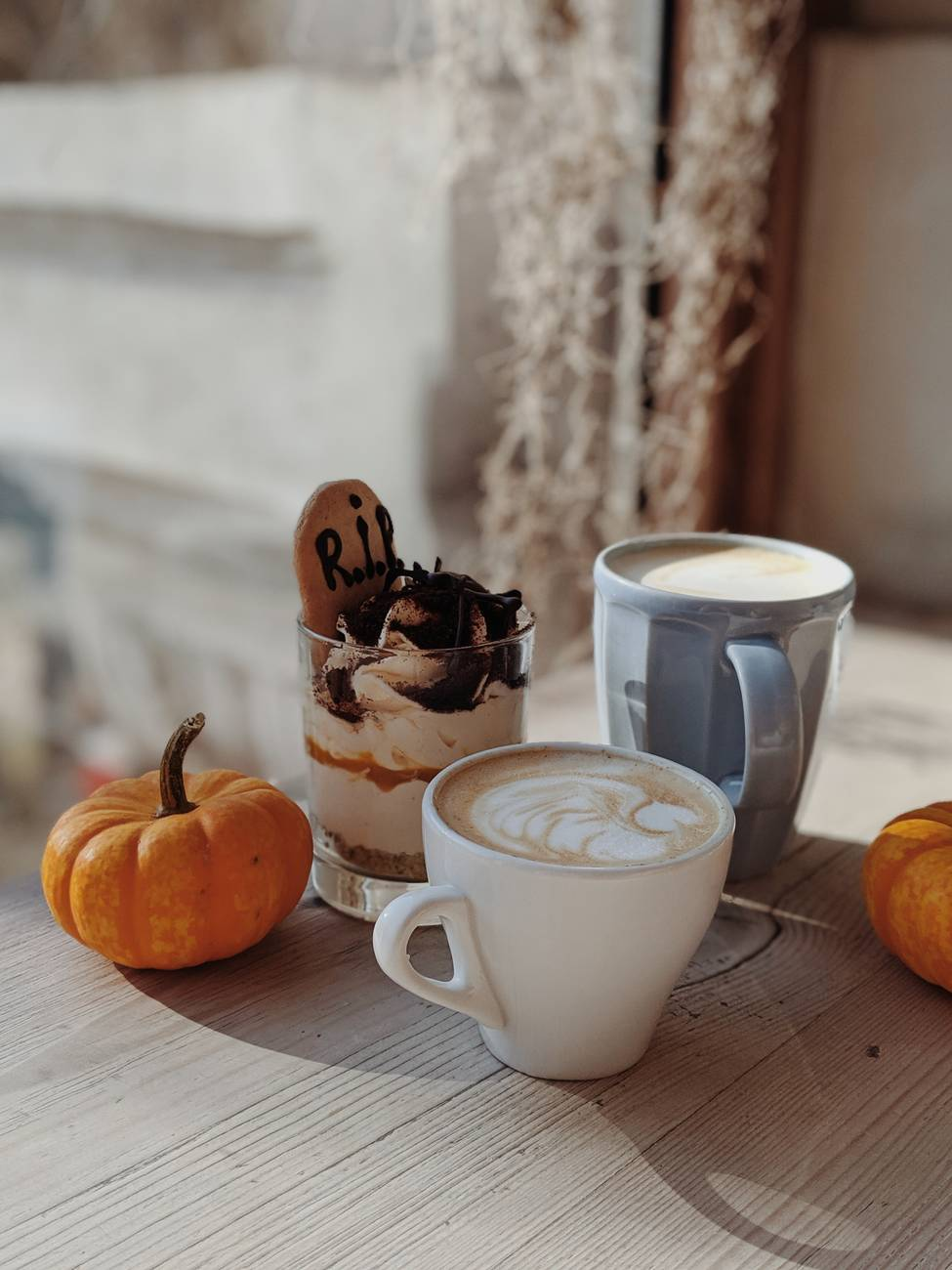 Picture of cups of coffee with foam and small pumpkins.