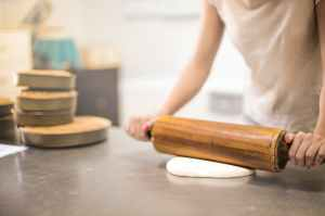 Picture of a person rolling dough.
