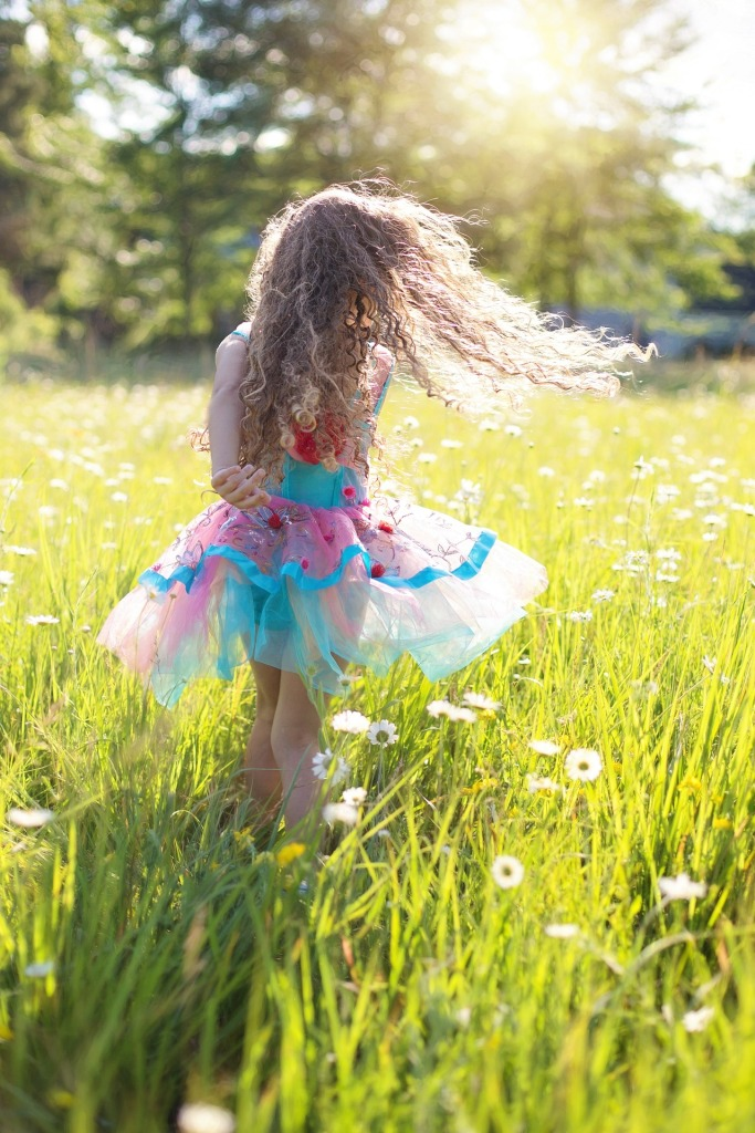 little girl with long hair and a tutu dancing in a meadow of daisies.