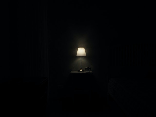 Picture of a small lamp on a nightstand shining in the darkness.