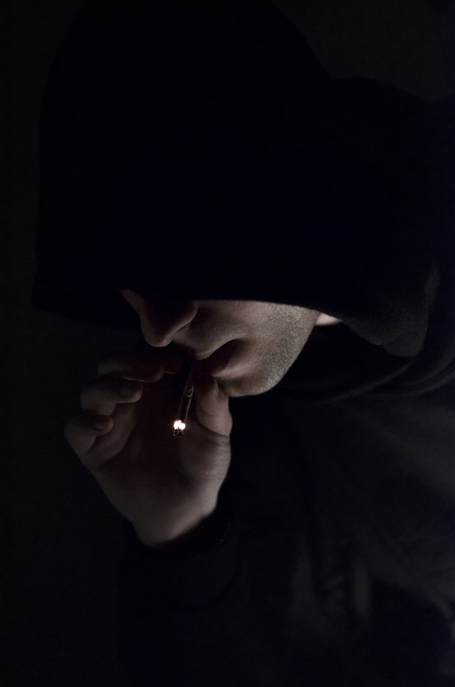 Picture of a hooded man smoking a cigarette.