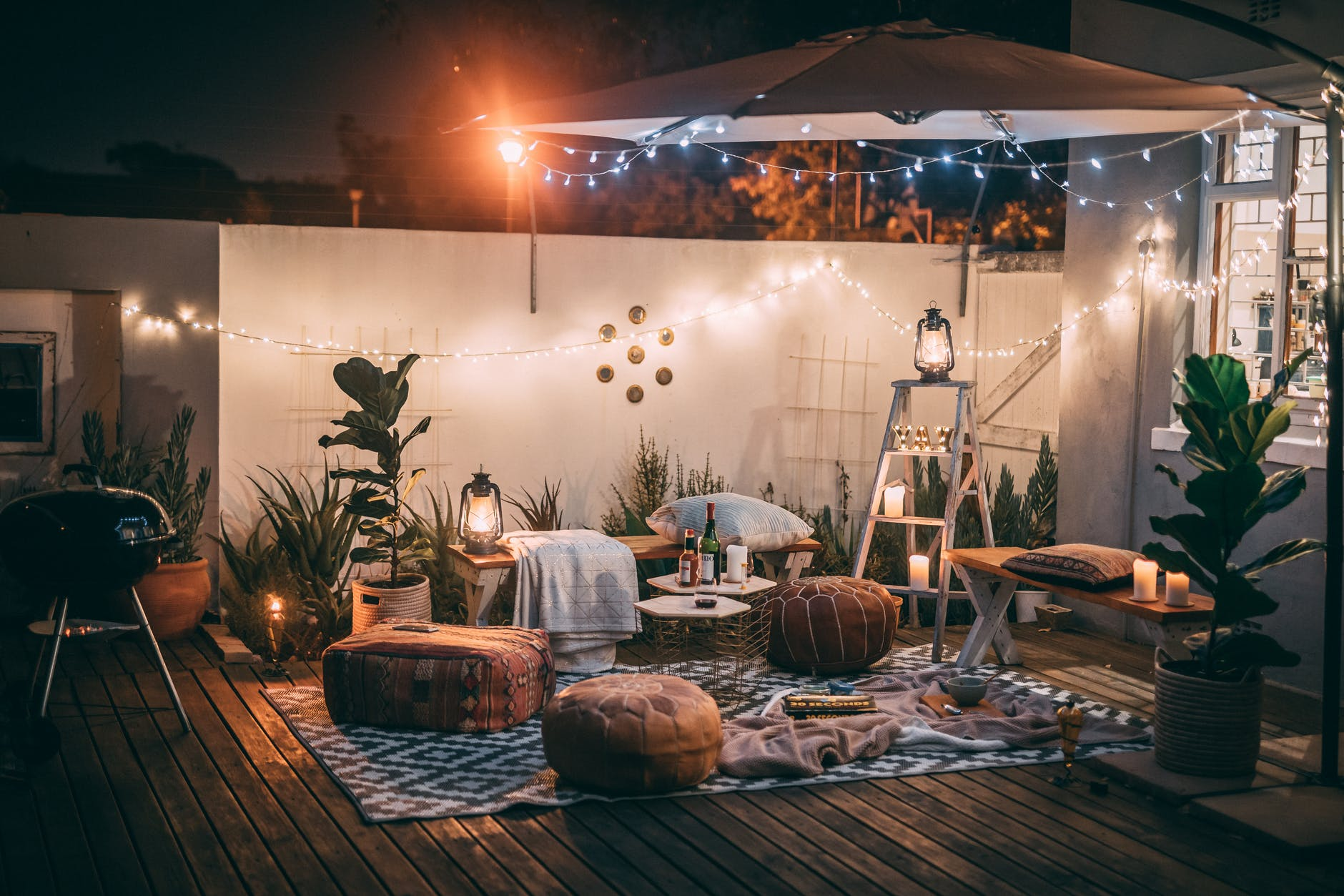 Photo Of Cushion Seats On Ground with string lights and barbeque grill.